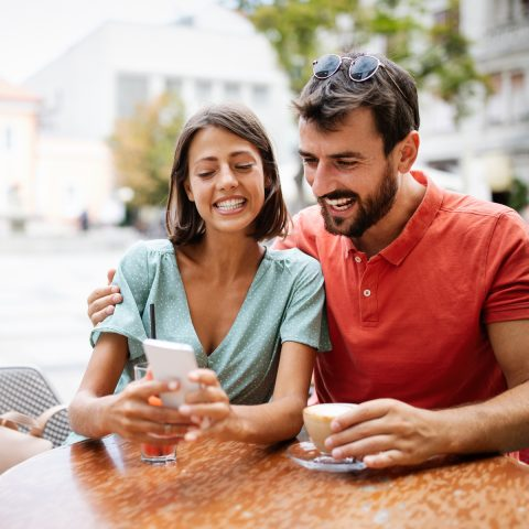embracing-couple-using-mobile-phone-smiling-and-ta-Z4PWH5M