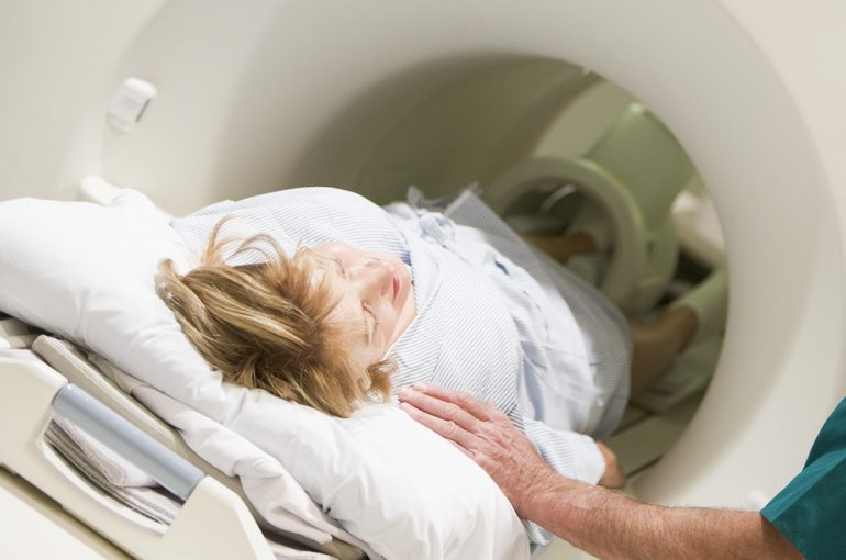 Doctor With Patient As They Prepare For A CAT Scan